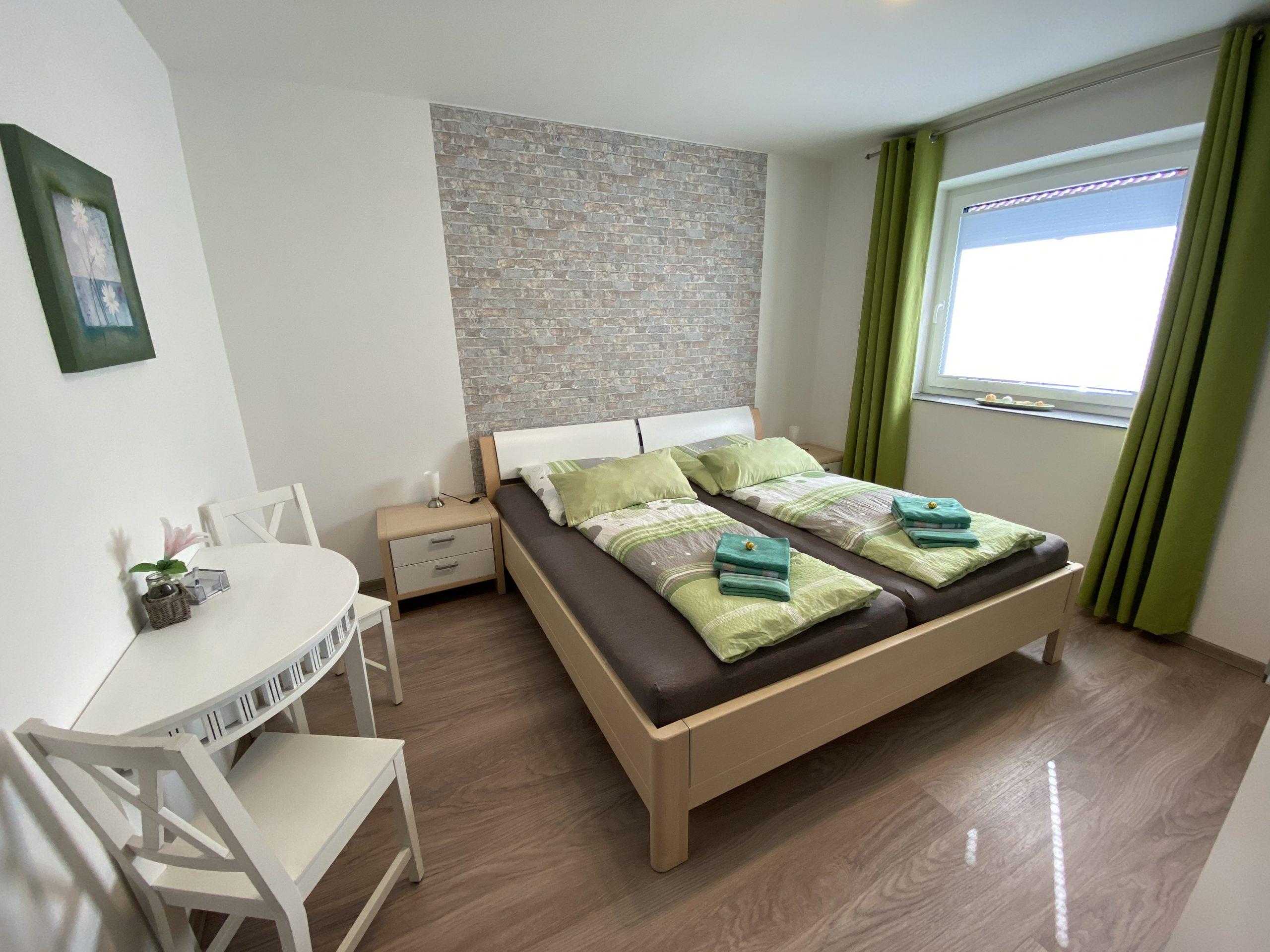 Dieses Schlafzimmer ist ca. 14 m² groß. Im Schlafzimmer befinden sich ein Doppelbett mit 200x200 cm und 2 Nachtschränke mit Nachttischlampen und einem Kleiderschrank. Der Raum wird bei Bedarf mit einem Verdunkelungsvorhang verdunkelt.